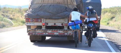 des cyclistes accrochés à un camion dans une côte